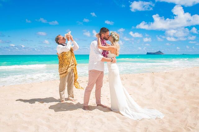A barefoot couple and officiant at a Hawaii beach wedding