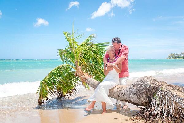 Newlyweds posing on Waialae Beach in Hawaii