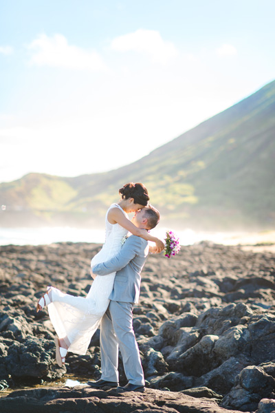 Newlyweds kissing on lava rocks