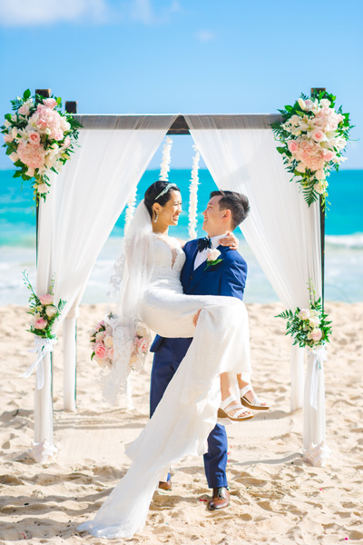 A groom lifting his wife at a Hawaii beach elopement
