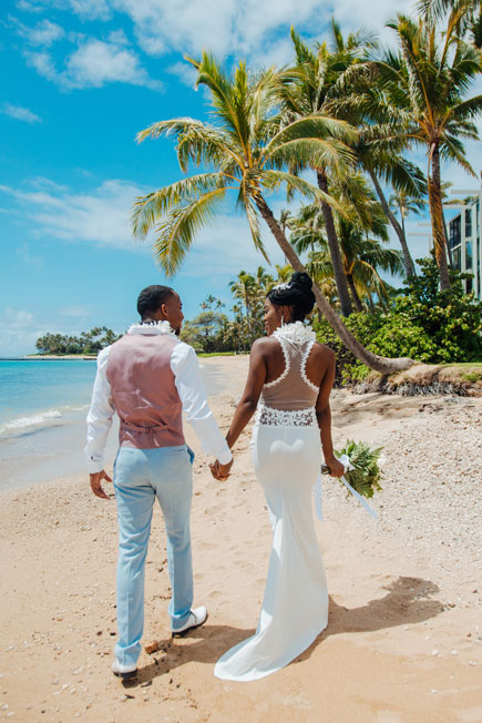 The back of a lacy beach wedding dress on a bride in Hawaii