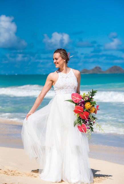 Bride modeling a beach wedding dress on the beach in Hawaii