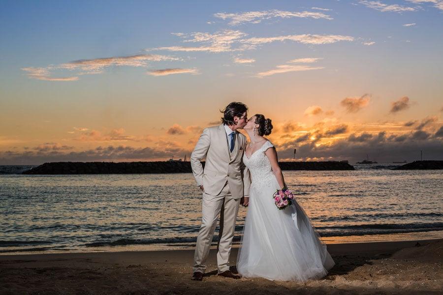 Newlyweds kissing on a beach in Hawaii