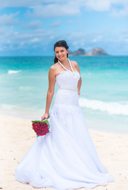 A bride holding a bouquet on the beach in Hawaii