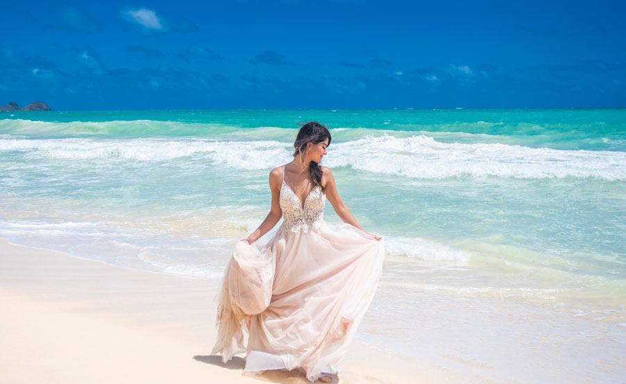 A bride spinning her wedding dress on the beach