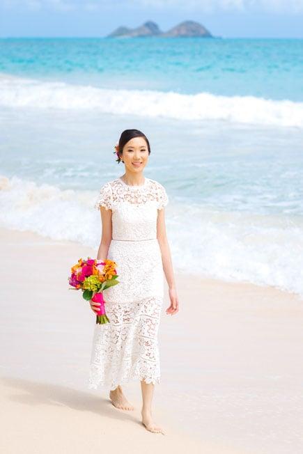 A bride in Hawaii wearing a lace wedding dress