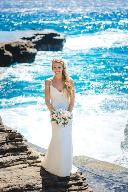 A bride in Hawaii posing with her bouquet