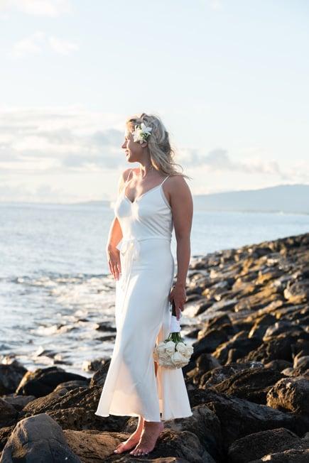 A bride in Hawaii standing on lava rocks