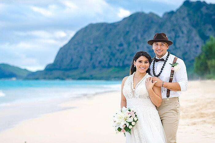 Newlyweds posing for a photo on the beach in Hawaii