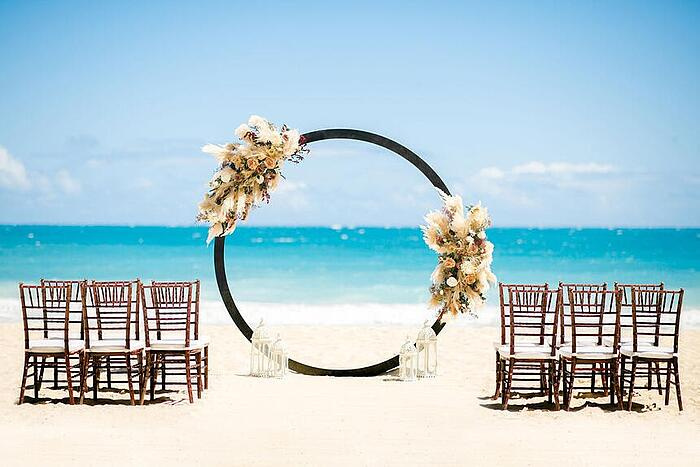 A Hawaii beach wedding setup with a circle arch and twelve chairs