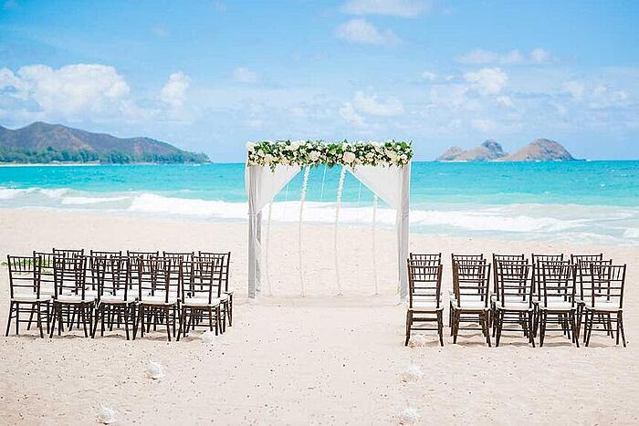 Hawaii beach wedding setup with 30 chairs and an arch with flowers