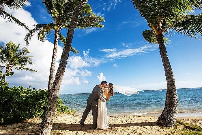 Newlyweds kissing after their beach wedding in Hawaii under palm trees