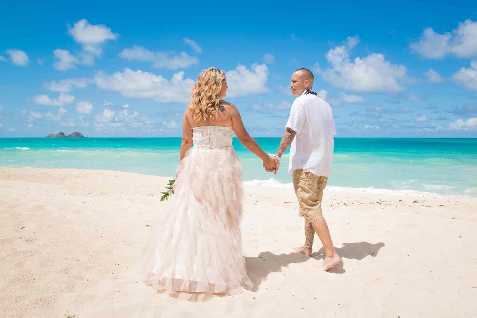 Newlyweds walking on a beach in Hawaii