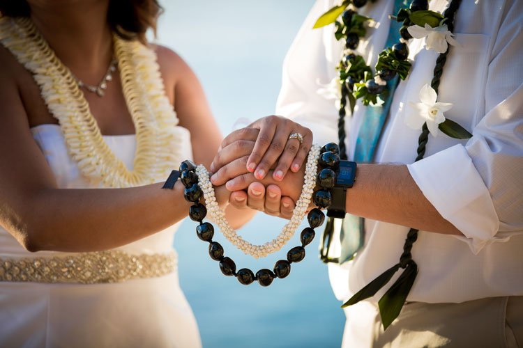 A wedding couple holding leis in Hawaii