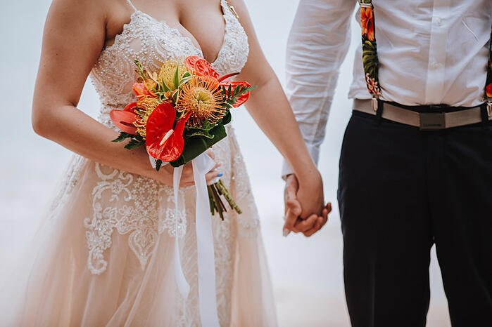 Bride holds a tropical bridal bouquet at a beach wedding at Kawela Bay