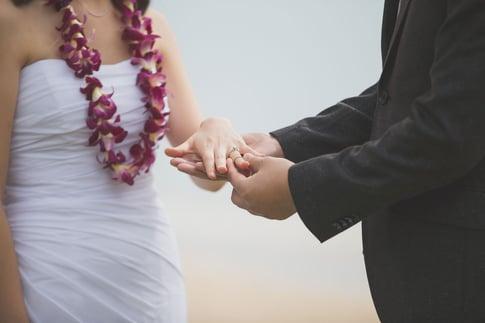 Hawaiian wedding ring exchange on a beach