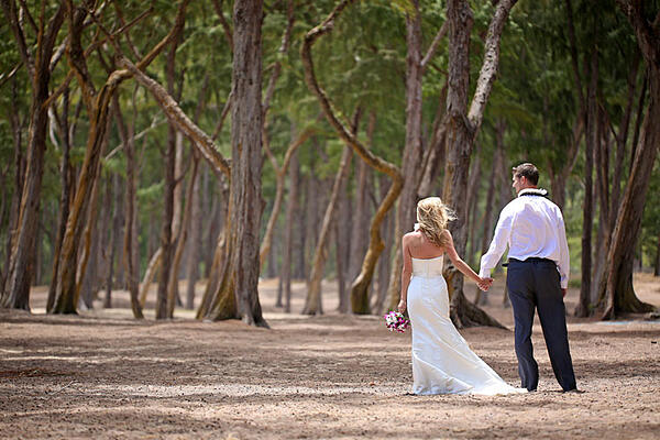 Bride and groom waking into the forest at their Hawaii wedding