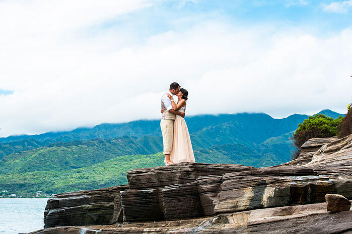 Newlyweds kissing on lava rocks in Hawaii