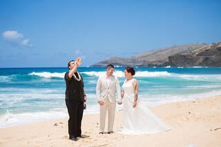 Officiant and couple at a Hawaii beach wedding