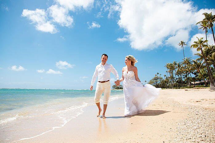 Eloping couple walking on a beach in Hawaii