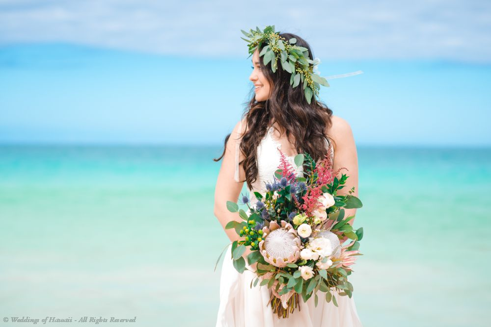 A bride in Hawaii wearing a haku lei and holding a bridal bouquet