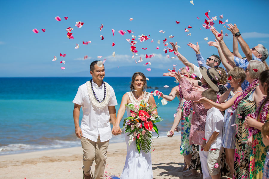 Small wedding group tossing flowers on a Maui beach